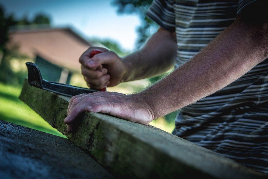 Menuisier qui ddécoupe une planche de bois